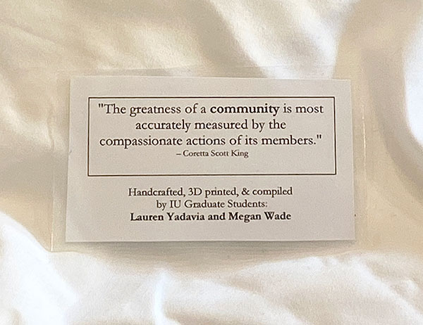 "An image of the laminated message attached to the PPE the students distribute. The message reads, ""The greatness of a community is most accurately measured by the compassionate actions of its members"" ~ Coretta Scott King"